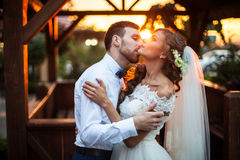 Romantic valentynes couple of newlyweds hugging at kissing at sunset near a wooden house Royalty Free Stock Photos