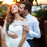Romantic valentynes couple of newlyweds hugging at kissing at sunset near a wooden house Stock Photo