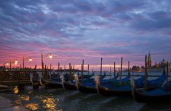Romantic Venice Sunrise with Gondolas. Romantic view of Venice with lampposts and gondolas near San Mark's Square with an early morning sunrise and San Giorgio Royalty Free Stock Photo