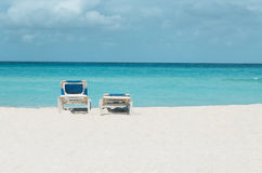Romantic view of the Caribbean beach, two beach chairs against blue sky Royalty Free Stock Photo