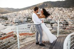 Romantic view of happy couple in white clothes. Beautiful landscape of sun above city during sunset. stock photos