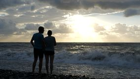 Cheery young family standing on the Black Sea shore at sunset in slo-mo. Romantic view of a happy young couple enjoying the stormy sea beach with foamy waves stock footage