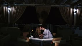 The romantic view of the kissing couple in the dark restaurant.