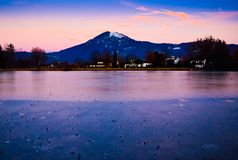 Romantic view of sunset of snowy mountain with frozen lake water in winter time in Europe royalty free stock image
