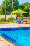 Romantic view of two sunbeds at swimming pool Royalty Free Stock Images