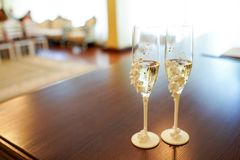 Romantic view of wedding glasses with champagne on dark table with copy space. Two crystal glasses decorated with white flowers. stock photography
