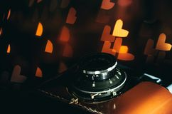 Old camera and festive romantic background with hearts. Romantic vintage background. Vintage camera and glowing heart-shaped festive light bulbs. Imagination and stock photos