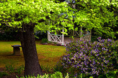 Romantic vintage gazebo in the garden. Vintage gazebo in the garden. Romantic wooden pergola in a green park among trees and flowers Stock Photo