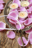 Romantic vintage keys and scented candles among pink rose petals Stock Photo