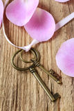 Romantic vintage keys and scented candles among pink rose petals Royalty Free Stock Images