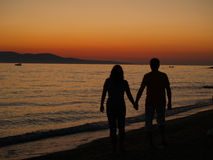 Romantic walk on the beach at sunset. Stock Photos