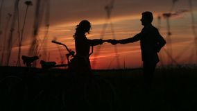 Romantic walk of the couple in love dancing in the field during the bright red sunset. View of the silhouettes