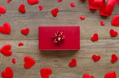 Romantic wedding anniversary gift concept. Felt red hearts, and gift box on a wooden table royalty free stock images