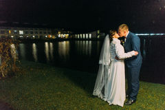 Romantic wedding. Bride and groom kissing near night lake illuminated with bright light from banquet hall windows Stock Images
