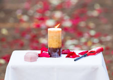 A romantic wedding ceremony with a lit candle, wedding bands, and an aisle full of red and white rose pedals. Closeup of candle. Red and tan color theme Stock Photo