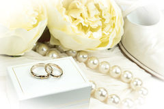 Romantic Wedding Concept: pair of gold rings on white box, pearl necklace, shoe and flowers. Stock Photos