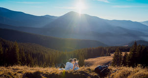 Romantic wedding couple kissing while lying on the grass in mountains Royalty Free Stock Images