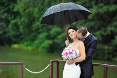 Romantic wedding couple kissing in a rainy day Stock Images