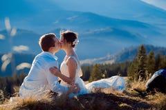 Romantic wedding couple kissing on the top of mountain Stock Photos