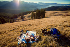 Romantic wedding couple lying on the grass in mountains. Royalty Free Stock Photo