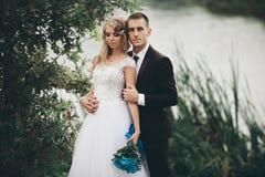 Romantic wedding couple, man and wife, posing near beautiful lake Stock Photography