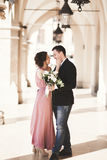 Romantic wedding couple, man and wife, posing near old building column. Romantic wedding couple, men and wife, posing near old building column stock images