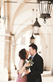 Romantic wedding couple, man and wife, posing near old building column. Romantic wedding couple, men and wife, posing near old building column royalty free stock photography