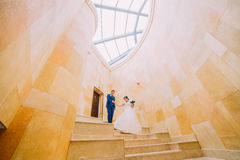 Romantic wedding couple on marble stairs with sandstone walls at background. Low angle Stock Images