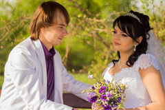 Romantic wedding couple sitting on a bench in the Royalty Free Stock Photography