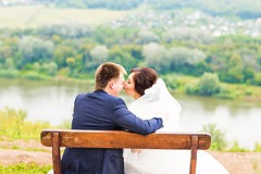 Romantic wedding couple sitting on a bench in the park Royalty Free Stock Photos