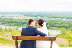 Romantic wedding couple sitting on a bench in the park Stock Images