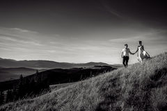 Romantic wedding couple walking in the mountains. Black and white photo Royalty Free Stock Image