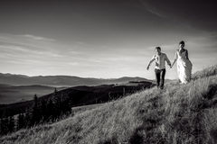 Romantic wedding couple walking in the mountains. Black and white photo Stock Image
