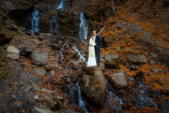 Romantic wedding couple. Waterfall on background. Honeymoon in the mountains Royalty Free Stock Photos