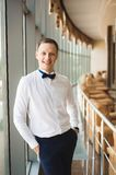 Romantic wedding moment, smilling groom near the window. royalty free stock photography