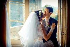 Romantic wedding portrait of attractive stylish newlyweds tenderly hugging and touching faces at the background of the. Window Stock Images