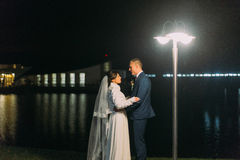 Romantic wedding portrait. Bride and groom holding each other near night lake illuminated with lights from banquet hall Stock Photos