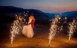 Romantic wedding shot of the kissing newlyweds. The groom is lifting up the bride on the mountains decorated with. Burning fireworks stock photo