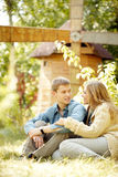 Romantic weekend. Two young people sitting on grass by mill Royalty Free Stock Photos
