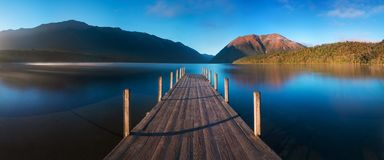 Romantic wharf on Lake Rotoiti, view ovelooking misty Saint Arnaud Ridge, all part of Nelson Lakes National Park in north od South stock photography