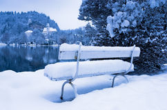 Romantic white bench covered with snow on a lake Bled in Slovenian Alps Royalty Free Stock Image