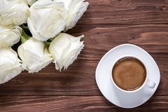Romantic white bouquet of white roses with cup of coffee on the wooden table Stock Images