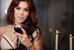 Romantic Wine. Beautiful young brunette with glass of red wine and candles Stock Images