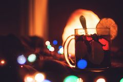 Romantic Winter evening hot drink, Christmas Eve. Glass transparent Cup of tea near window in dark blurred background with lamp. And multicolored garland bokeh royalty free stock images