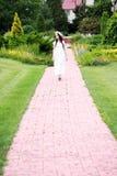 Romantic woman. Beautiful brunette romantic woman with flower wreath walking in the beautiful garden Royalty Free Stock Photo