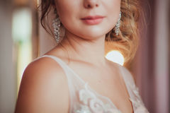 Romantic Woman in bridal dress with wedding bouquet standing against the light. close-up. Indoor, interior, studio.  Royalty Free Stock Photography