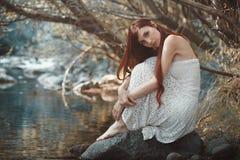 Romantic woman close to a stream. Romantic woman posing close to stream waters Stock Photo