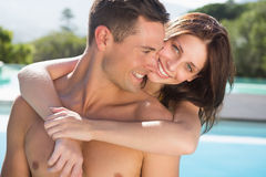 Romantic woman embracing man by swimming pool Stock Photography