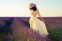 Romantic woman in fairy lavender fields. Pretty glamorous lady standing in a field of lavender flowers Royalty Free Stock Photography
