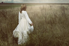 Romantic woman in the fields. With vintage dress. Purity and freedom Stock Photos